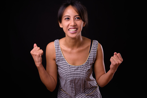 Portrait Of Happy Filipino Woman Smiling Against Black Background Stock Photo - Download Image Now