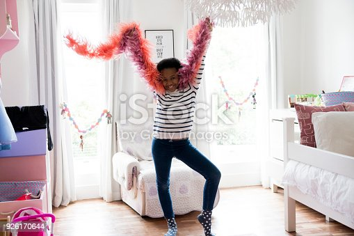 Portrait of girl with feather boas dancing at home. She is wearing striped casuals. Female dancer is smiling.