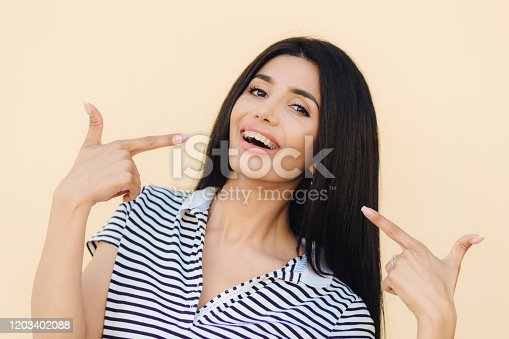 Portrait of happy gorgeous female model indicates with fore fingers at her face, advertises braces for even teeth, has dark long straight hair, shining eyes and perfect healthy skin, models indoor