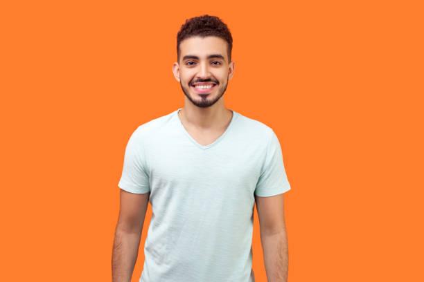 Portrait of happy handsome brunette man looking at camera with joyful attractive toothy smile. indoor studio shot isolated on orange background stock photo