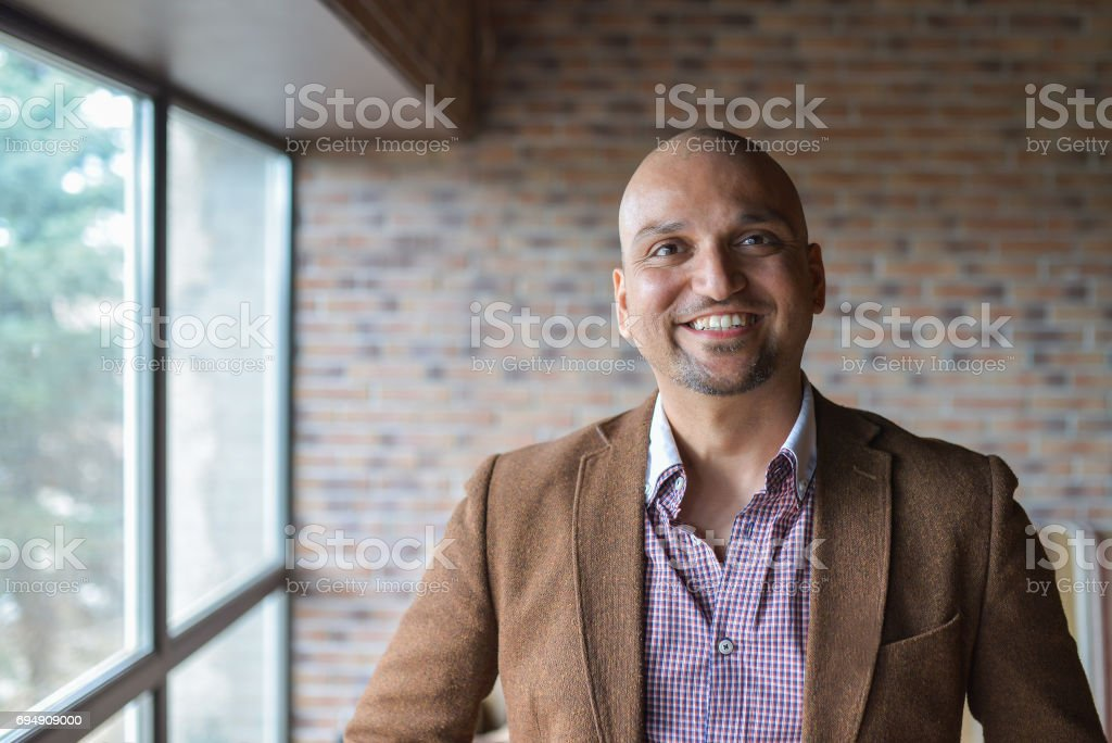 Portrait of happy handsome indian business man, smiling, confident and friendly indoors. stock photo