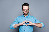 istock Portrait of happy handsome man in glasses making heart with fingers 944980386