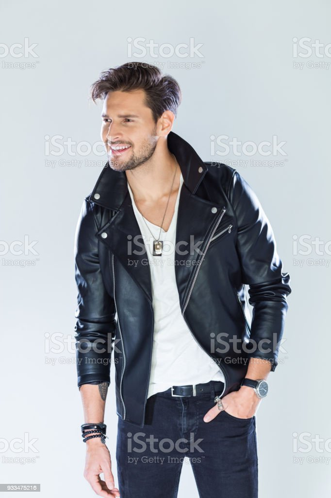 Portrait of happy handsome man wearing leather jacket Fashion portrait of handsome man wearing black leather jacket, looking away and smiling. Studio shot, grey background. 25-29 Years Stock Photo