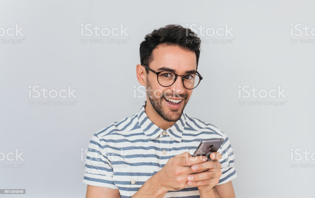 Portrait of happy handsome surprised male wearing striped shirt and reound spectalces, using smart phone for texting messages having pleasant smile showing white teeth, had amazed face for good news. stock photo