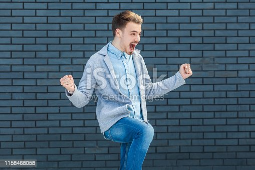 istock Portrait of happy handsome young blonde man in casual style standing, amazed, celebrating and rejoicing his victory and success with screaming happy face. 1158468058