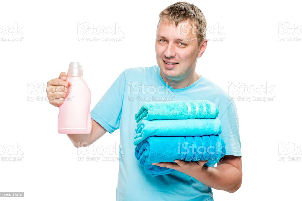 portrait of happy husband with clean towels and gel for washing clothes on white background zbiór zdjęć royalty-free