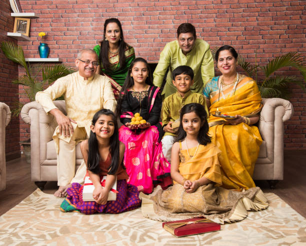 portrait of happy indian family in traditional wear sitting on sofa indoor - diwali stock pictures, royalty-free photos & images