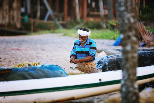 Varkala, India - February 09, 2016: Portrait of happy Indian fisherman unravels fishing nets and tackle while sitting in a boat, Kerala India Fishery Gulf. Odayam beach, Varkala, India