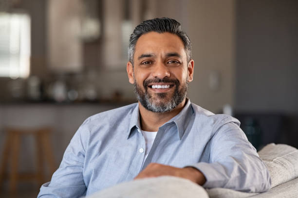 Portrait of happy indian man smiling at home stock photo