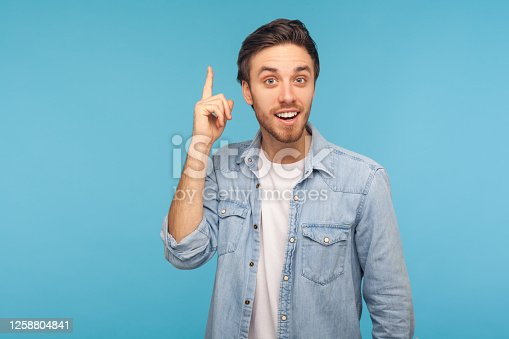 Portrait of happy inspired man in worker denim shirt raising finger and having genius idea, looking amazed by sudden smart solution, creative thought. indoor studio shot isolated on blue background