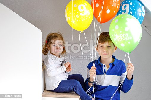 istock Portrait of happy kid boy and cute little toddler girl with bunch on colorful air balloons on birthday. Smiling happy school child and sister having fun, celebrating birthday. Family party 1138221883