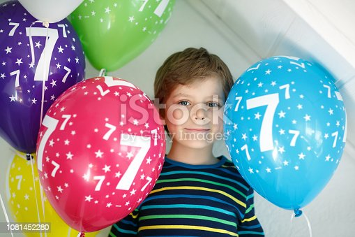 istock Portrait of happy kid boy with bunch on colorful air balloons on 7 birthday. Smiling school child having fun, celebrating seventh birth day. Family and best friend party 1081452280