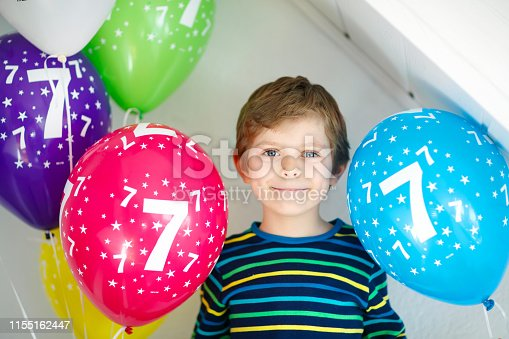 istock Portrait of happy kid boy with bunch on colorful air balloons on 7 birthday 1155162447