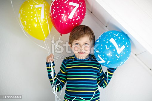 istock Portrait of happy kid boy with bunch on colorful air balloons on 7 birthday 1172200004