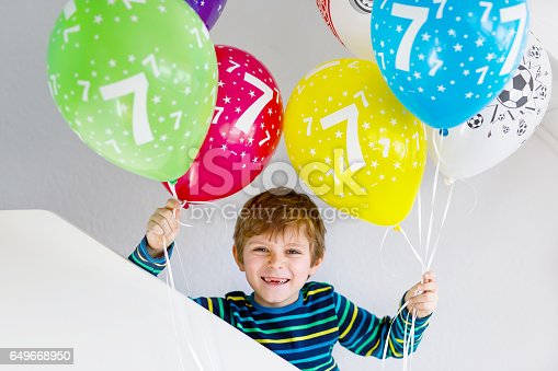 istock Portrait of happy kid boy with bunch on colorful air balloons on 7 birthday 649668950