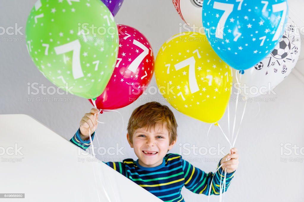 Portrait of happy kid boy with bunch on colorful air balloons on 7 birthday stock photo