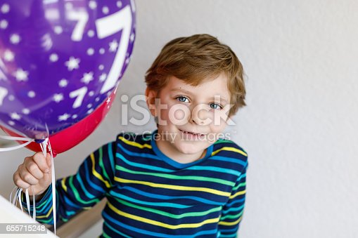 istock Portrait of happy kid boy with bunch on colorful air balloons on 7 birthday 655715248
