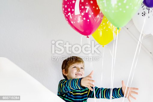istock Portrait of happy kid boy with bunch on colorful air balloons on 7 birthday 655715284