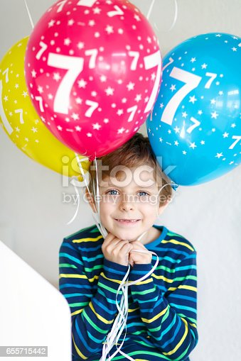 istock Portrait of happy kid boy with bunch on colorful air balloons on 7 birthday 655715442