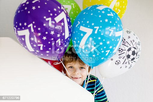 istock Portrait of happy kid boy with bunch on colorful air balloons on 7 birthday 671220796