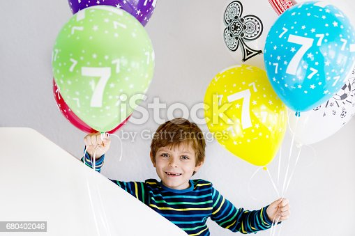 istock Portrait of happy kid boy with bunch on colorful air balloons on 7 birthday 680402046