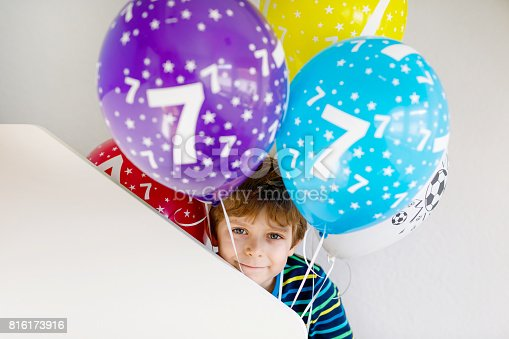 istock Portrait of happy kid boy with bunch on colorful air balloons on 7 birthday 816173916