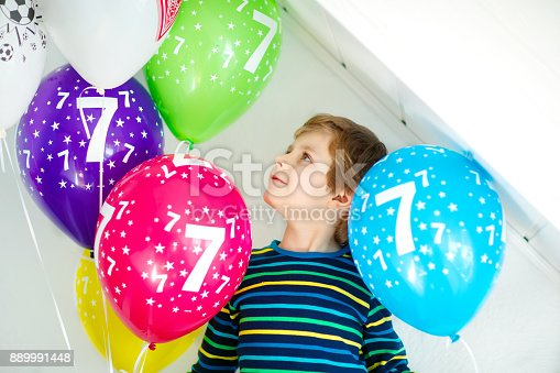 istock Portrait of happy kid boy with bunch on colorful air balloons on 7 birthday 889991448