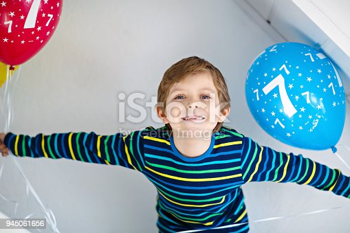 istock Portrait of happy kid boy with bunch on colorful air balloons on 7 birthday 945061656