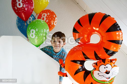istock Portrait of happy kid boy with bunch on colorful air balloons on 8 birthday 933458532