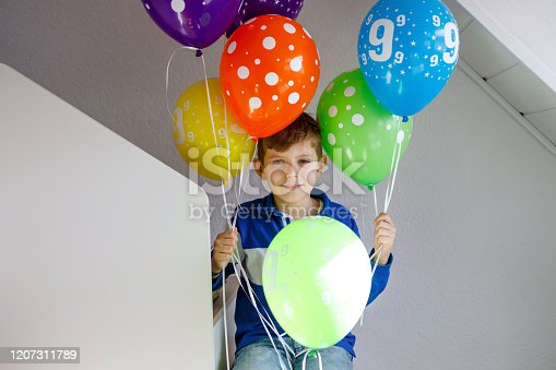 933458532 istock photo Portrait of happy kid boy with bunch on colorful air balloons on his birthday. Smiling school child having fun, celebrating nineth birth day. Family and best friend party 1207311789