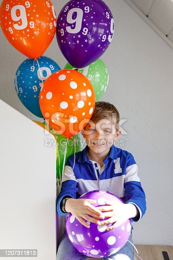 933458532 istock photo Portrait of happy kid boy with bunch on colorful air balloons on his birthday. Smiling school child having fun, celebrating nineth birth day. Family and best friend party 1207311813