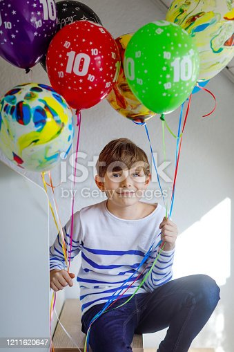 933458532 istock photo Portrait of happy kid boy with bunch on colorful air balloons on his birthday. Smiling school child having fun, celebrating tenth birth day. Family and best friend party 1211620647