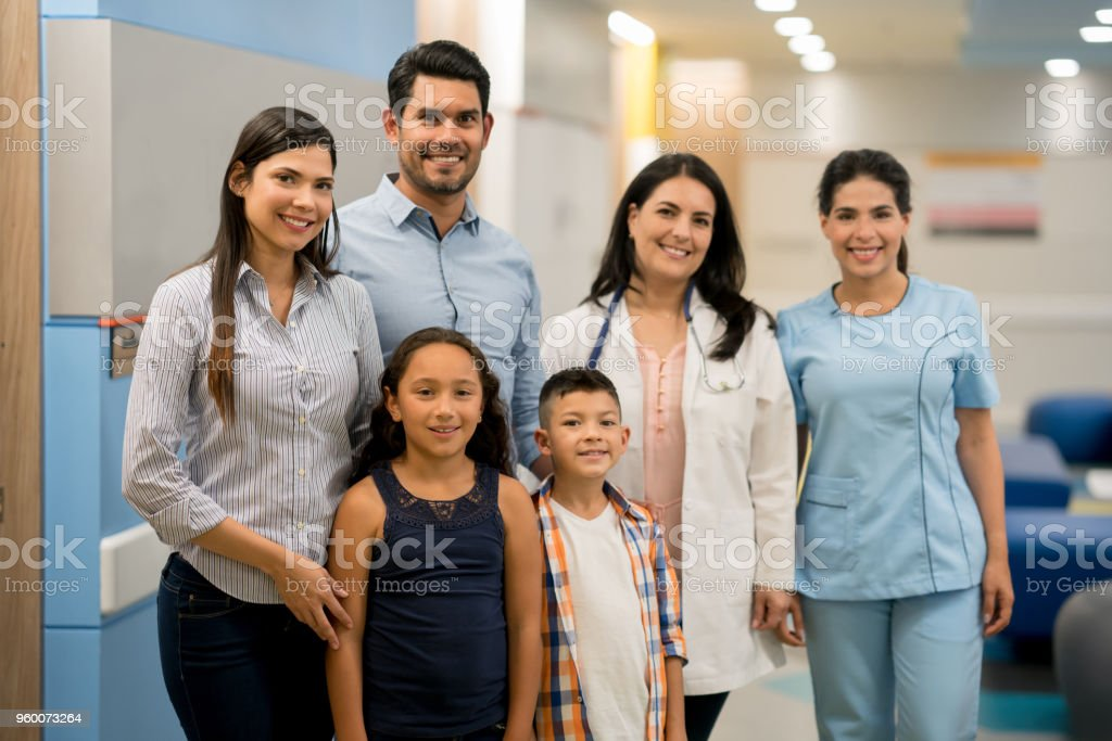 Portrait of happy latin american family with doctor and nurse at the hospital all looking at camera smiling stock photo