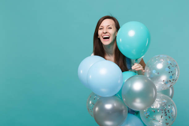 Portrait of happy laughing cute young woman in denim clothes celebrating and holding colorful air balloons isolated on blue turquoise wall background. Birthday holiday party, people emotions concept. stock photo