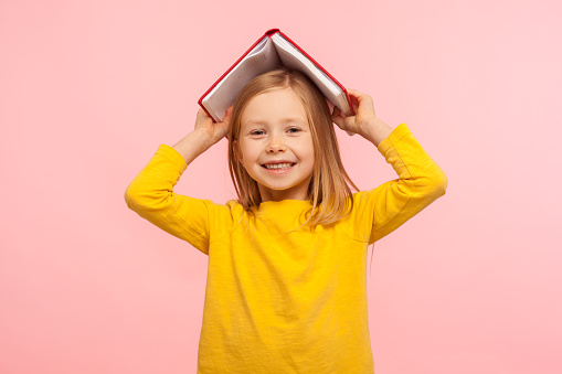 Portrait of happy lazy little girl covering head with book and smiling to camera, disobedient child having fun