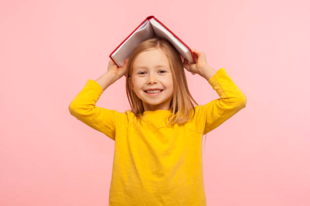 Portrait of happy lazy little girl covering head with book and smiling to camera, disobedient child having fun stock photo