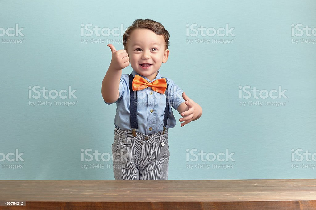 Portrait of happy little boy giving you thumbs up stock photo