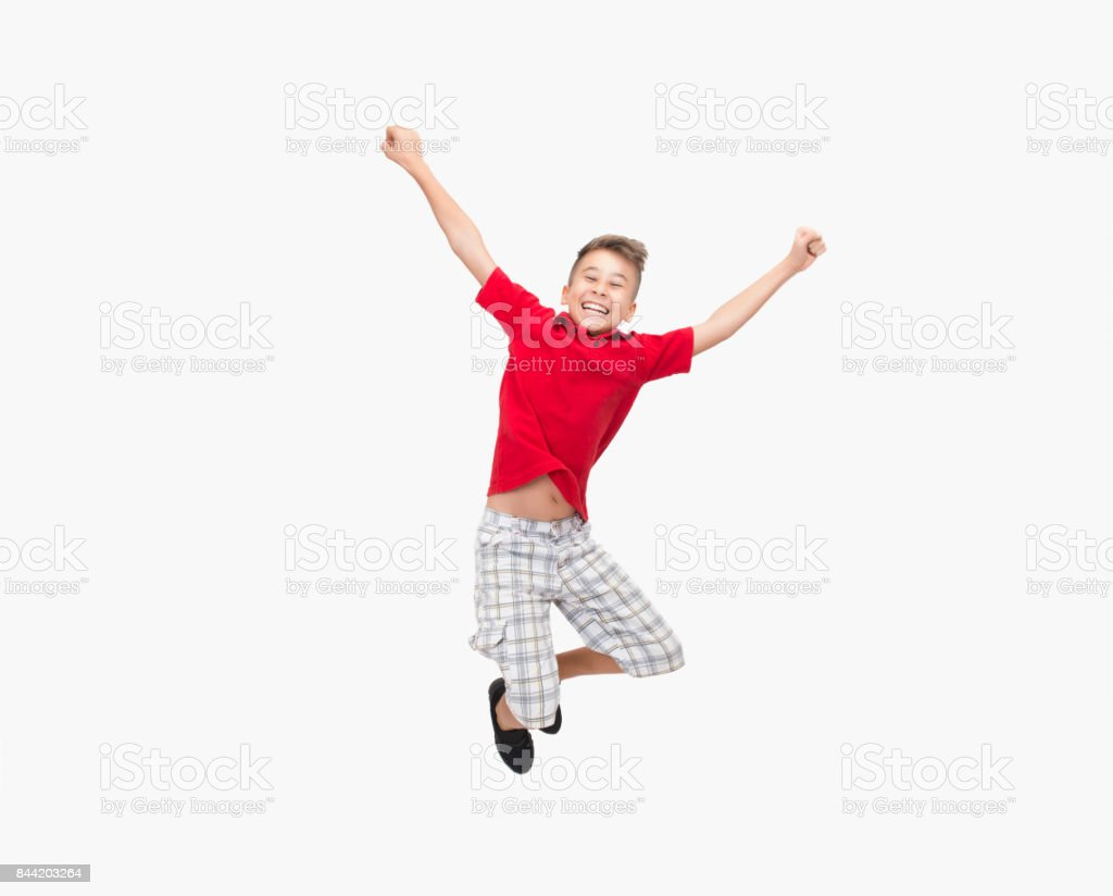 Portrait of happy little boy jumping on white background stock photo