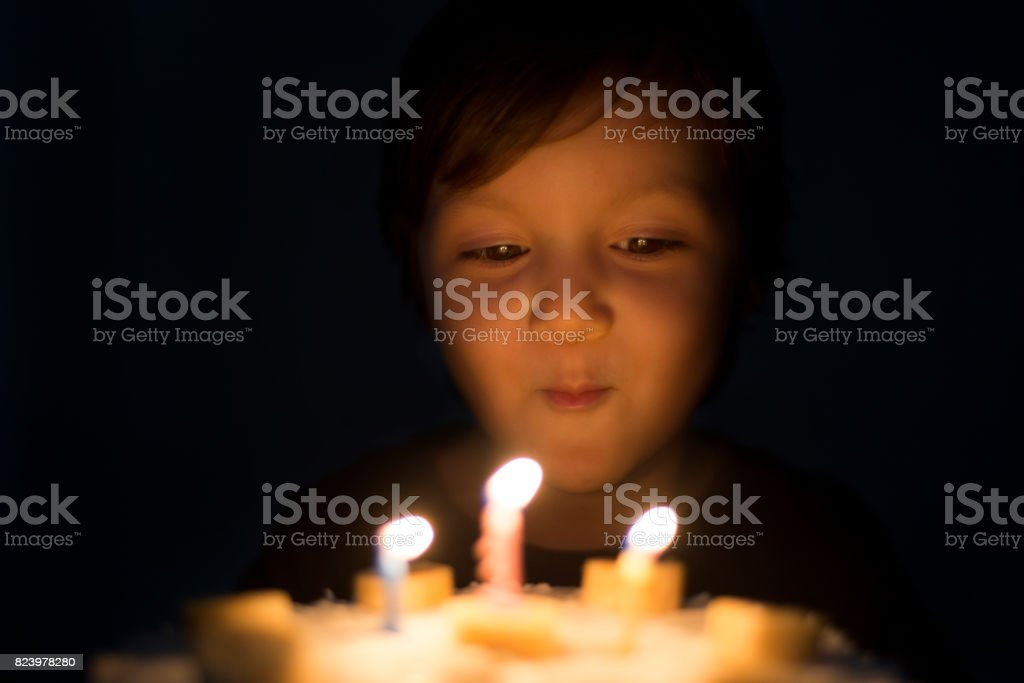 Portrait of happy little girl blowing out the birthday cake stock photo