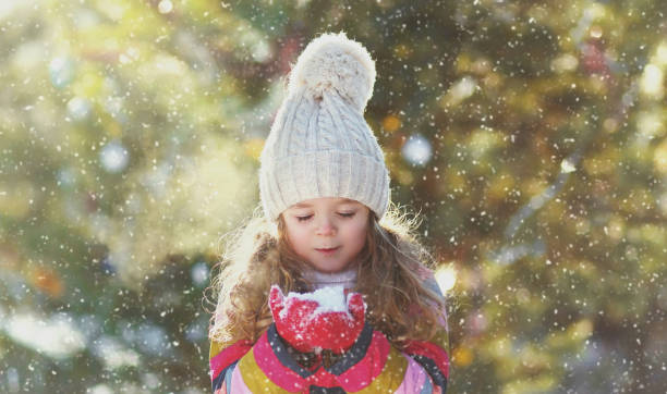 Portrait of happy little girl child in winter over snowy background stock photo