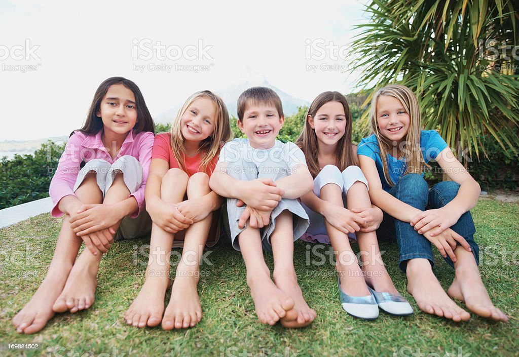 portrait of happy little kids sitting in a line on grass royalty free stock photo - Images Of Little Kids