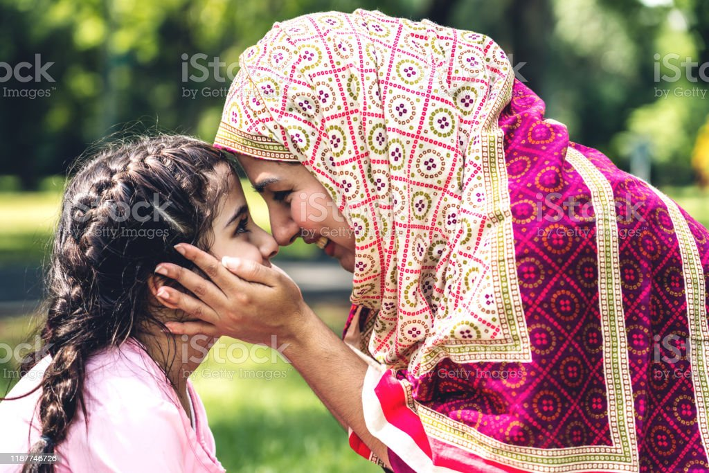 Portrait of happy lovely family arabic muslim mother and little muslim girls child with hijab dress smiling and having fun kissing together in summer park Portrait of happy lovely family arabic muslim mother and little muslim girls child with hijab dress smiling and having fun kissing together in summer park Arabia Stock Photo