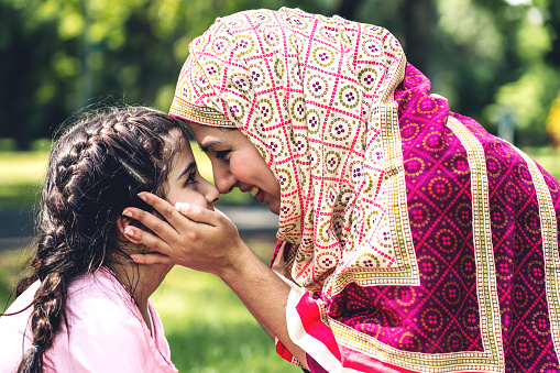 Portrait Of Happy Lovely Family Arabic Muslim Mother And Little Muslim Girls Child With Hijab Dress Smiling And Having Fun Kissing Together In Summer Park Stock Photo - Download Image Now