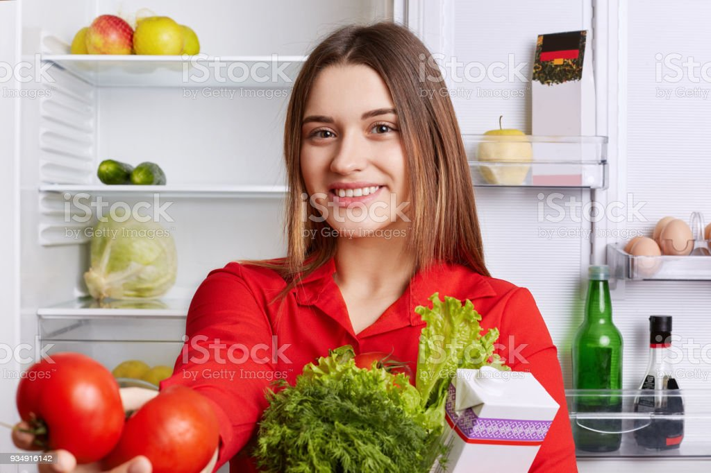 Portrait of happy lovely woman with cheerful expression dressed in red blouse, holds fresh vegetables, demonstrates red tomatoes, being glad to start new day, makes vegeterian salad for herself stock photo