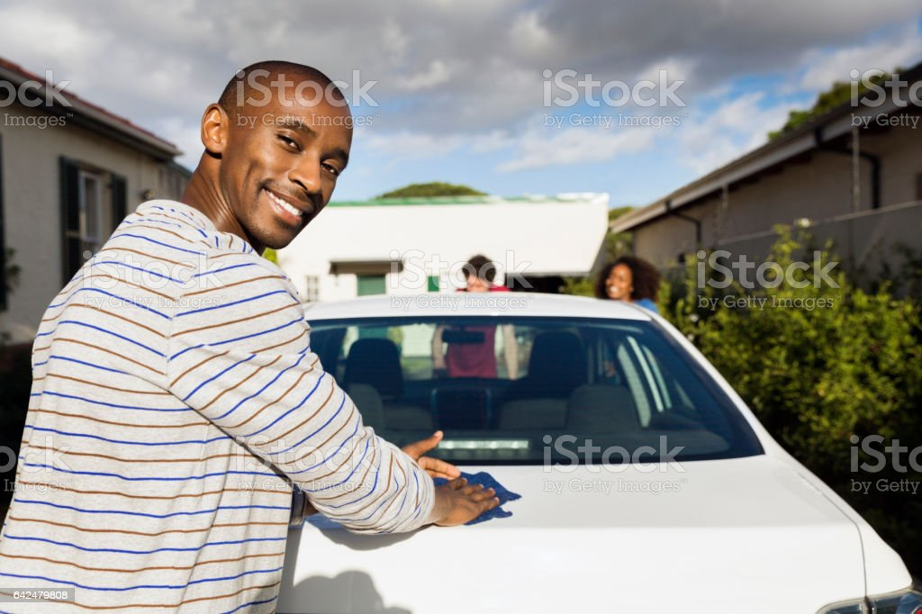 Portrait of happy man cleaning car at yard stock photo