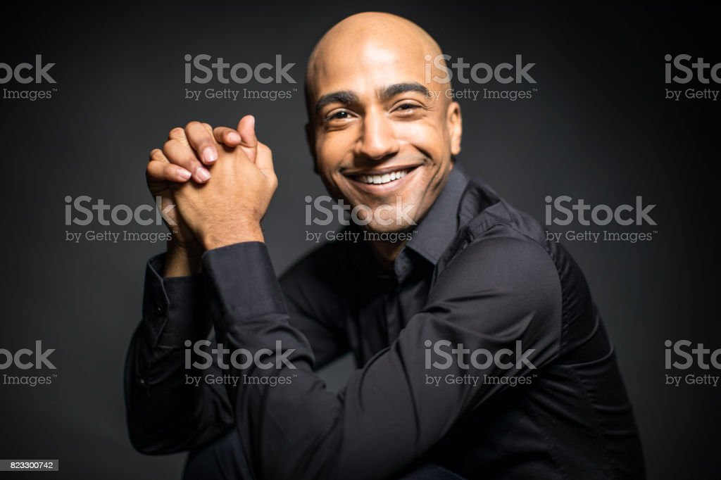 Portrait Of Happy Man Sitting With Hands Clasped stock photo
