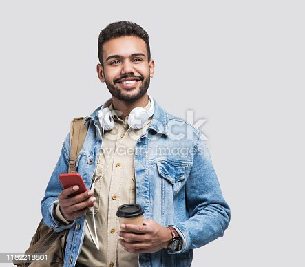 Studio shot of handsome smiling man using smartphone.