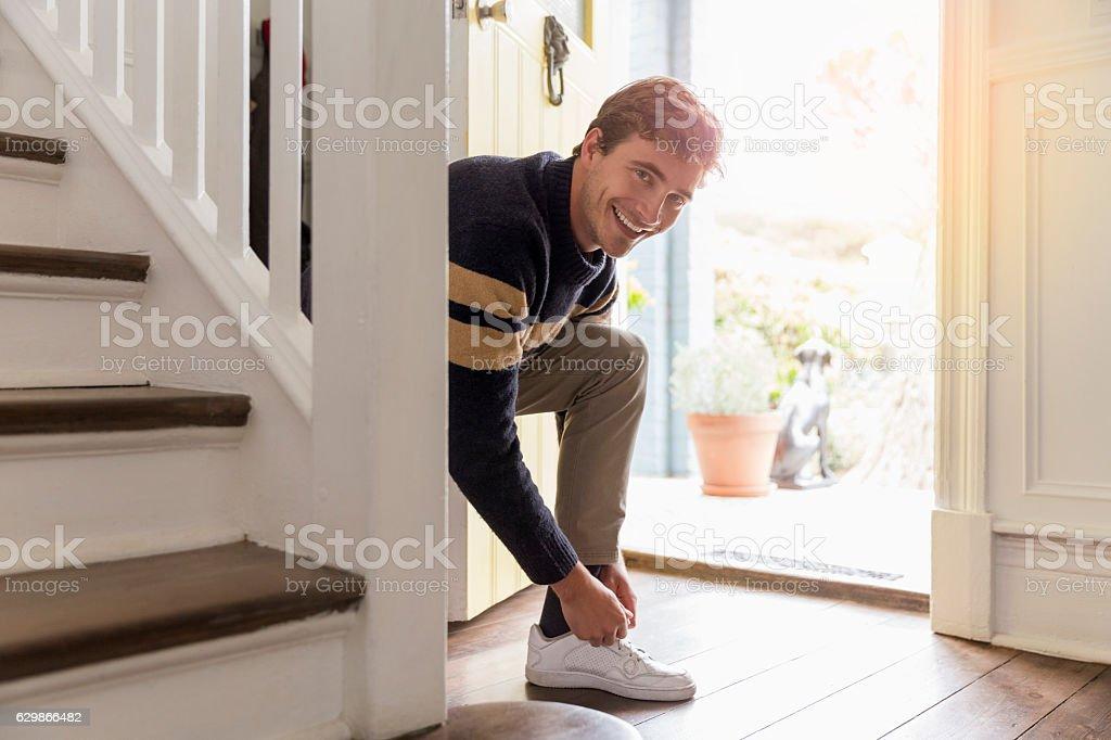 Portrait of happy man tying shoelace at doorway stock photo