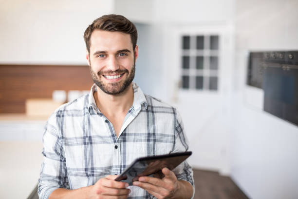 portrait of happy man using digital tablet - one young man only stock photos and pictures