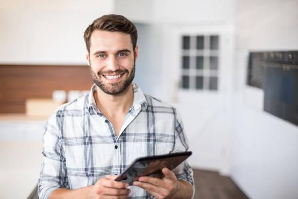 retrato de hombre feliz con tableta digital - un solo hombre joven fotografías e imágenes de stock